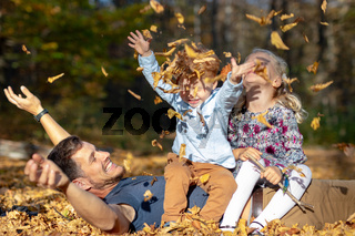 Happy dad and kids throwing up autumn leaves in park
