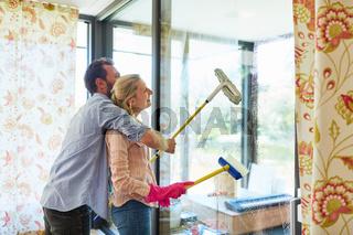 Paar mit Fensterwischer beim Fenster putzen