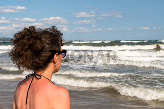 Young woman on the beach looking at the waves and enjoying the sea.