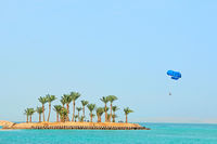 parasailing over tropical island in Red Sea. Tropical resort in Egypt. People rest on Egyptian resor