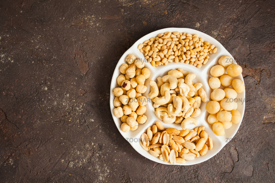 Big plate full of various nuts over black background, copy space