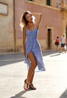 Beautiful young slim woman wearing long blue dress posing looking at camera standing in old streets of Murcia town, vertical image. Spain