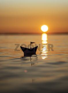 Papierschiff im Sonnenuntergang
