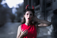Beautiful woman in red dress and horns. Halloween