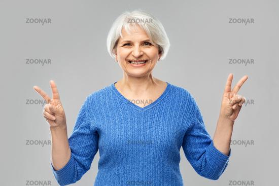 portrait of smiling senior woman showing peace