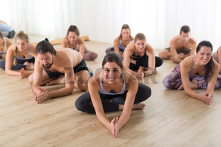 Group of young sporty attractive people in yoga studio, practicing yoga lesson with instructor, sitting on floor in forward band stretching yoga pose. Healthy active lifestyle, working out in gym