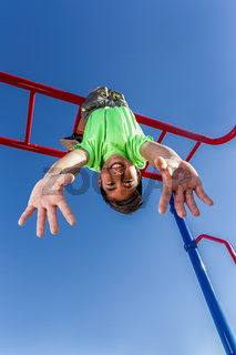 Boy hangs upside down while playing.
