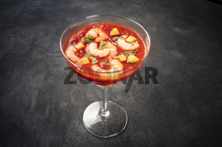 Coctel de gambas, Mexican shrimp cocktail with avocado, on a dark background with a place for text