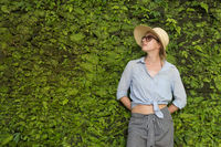 Portrait of a beautiful female traveler. Smiling young woman in summer hat wearing sunglasses, standing in front of lush tropical plant greenery wall background.