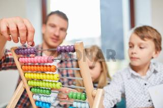 Vater und Kinder rechnen mit Abakus