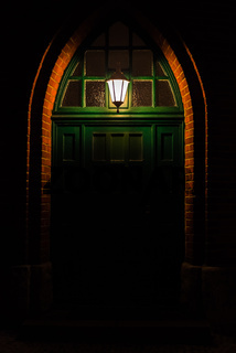 Old green wooden door with a single light