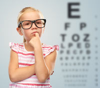 little girl in glasses over eye test chart