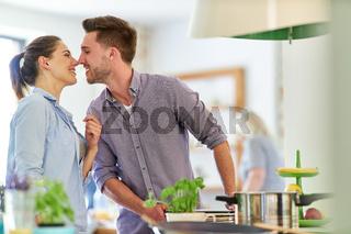 Junger Mann küsst seine Freundin in der Küche