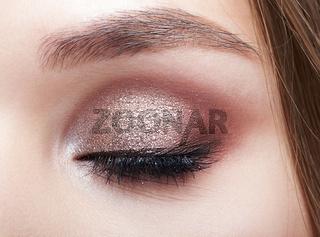 Closeup macro shot of closed human woman eye.