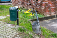 Two dumpsters of garbage and yellow bycicle