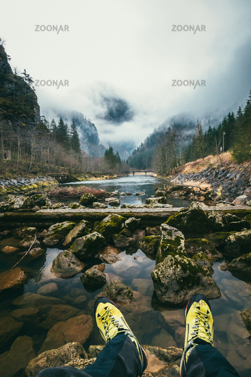 Travelers hiking boots on mountain near river on nature background.