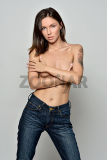 woman in jeans crossing arms on her naked bosom.