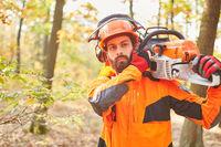 Forstwirt in Schutzkleidung mit Motorsäge