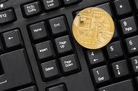 Golden BTC coin on computer keyboard