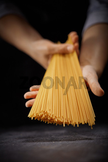 Italian long spaghetti in the hands of the cook on a dark background. The concept of cooking food