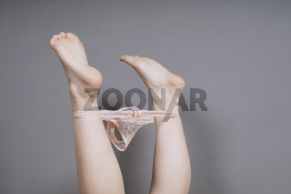 female feet in the air with thong panties around ankles