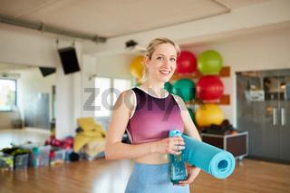 Frau als Trainer mit Yogamatte und Wasserflasche