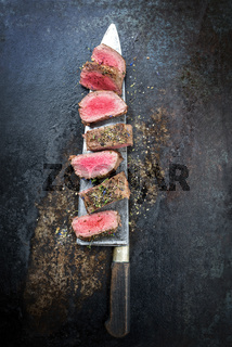 Traditional barbecue aged venison backstrap roast sliced with herbs as top view on a large knife with rustic background with copy space
