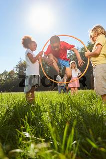 Kinder springen durch Reifen als Sport und Spiel