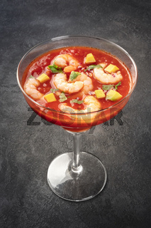 Coctel de camarones, Mexican shrimp cocktail with avocado, on a dark background