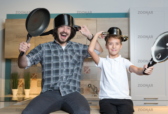 father and kid having great time in kitchen. Father and son having fun with kitchen pots. Concept of togethernes and family