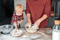 Dad and son make dough in the kitchen