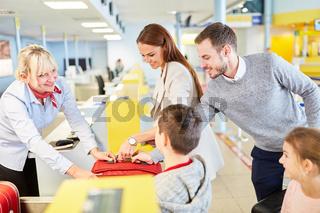 Familie mit Kindern am Flughafen Check-In Schalter