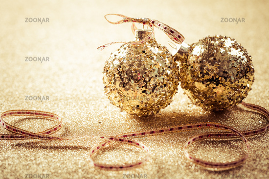 Golden christmas balls on glitter background with copy space.  Glitter background.