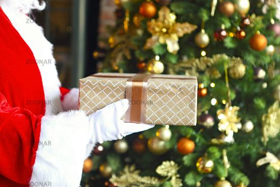 Santa Claus secretly putting gift box by the Christmas tree