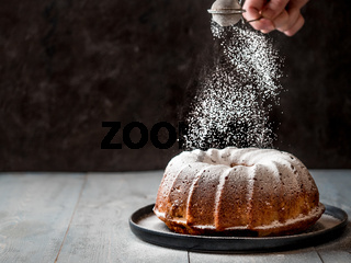 Female hand sprinkling icing sugar on muffin cake