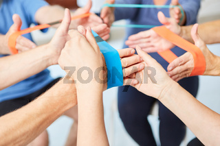 Trainer hilft bei Übung mit dem Elastikband