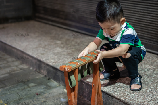Chinese boy playing with folding chair