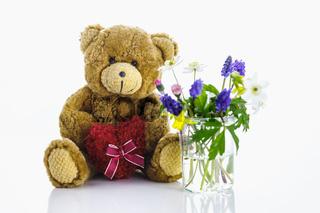 Ein Teddybär mit Herz neben einer Vase mit Blumen. Der Frühling ist da.
