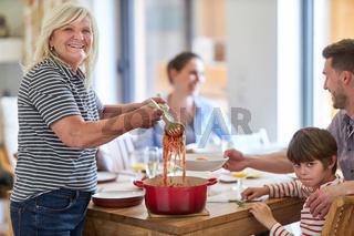 Oma am Esstisch beim Spaghetti verteilen