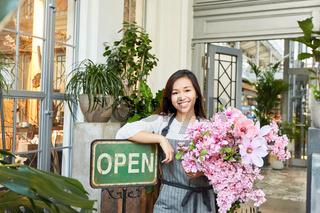 Floristin mit Blumenstrauß bei Blumenladen Eröffnung