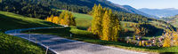 Light and shadows. Autumn Santa Magdalena Italy mountain village environs, grassy hills and secondary serpentine road. Picturesque traveling, seasonal and countryside beauty concept panorama view.