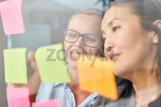 Business Frauen analysieren Ideen auf Zetteln