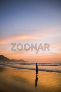 Young woman walking at the beach at sunrise in Ubatuba, Sao Paulo, Brazil