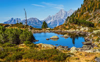 Sunny autumn alpine view. Peaceful mountain forest lake with clear transparent water and reflections. Obersee Lake