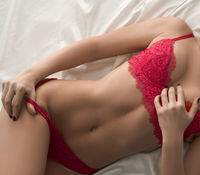 Top view of sensual girl in red lace lying in bed