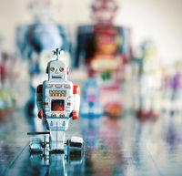 little silver robot on wooden floor  blured background