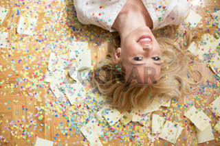 Cheerful young woman is stretching out her hands while confetti falling on her