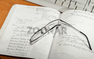 Notebook and glasses and keyboard