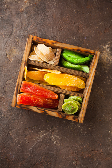 Tasty colorful dried fruits in a wooden box, top view