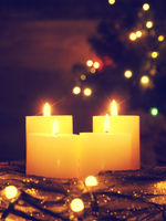 Four burning Advent candles with Christmas tree